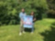 """Ein Mann und eine Frau halten ein Plakat mit der Aufschrift """"Vorsicht Schulkinder!"""" in die Kamera und lächeln freundlich."""