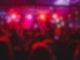 Viele Menschen stehen in einem wenig beleuchteten Club und tanzen und lachen zusammen.