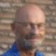 Ein Mann in blauem Hemd mit Brille vor einer Mauer