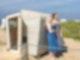 Zwei Frauen, mit Handtüchern bekleidet,lehnen an einem Strandkorb, der auch als Sauna nutzbar ist.