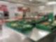 In einem Raum sind Gemüsekisten aufgebaut, im Hintergrund sind auch eine Fleischtheke und Backwaren zu sehen.