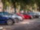 Mehrere Autos parken in einer Reihe unter Bäumen
