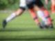 Zwei Männer spielen Fußball und dribbeln um einen Ball.