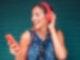 Musiktest: eine junge Frau hat Kopfhörer auf, schaut auf ihr Smartphone und lacht.