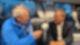 Carsten Kock sitzt mit R.SH-Mikrofon und Sturmfrisur an einem Tisch in einem Bus. Neben ihm sitzt Armin Laschet und schaut ihn an.