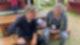 Carsten Kock sitzt mit R.SH-Mikrofon auf einer Bank. Neben ihm sitzt Robert Habeck und spricht ins Mikrofon.